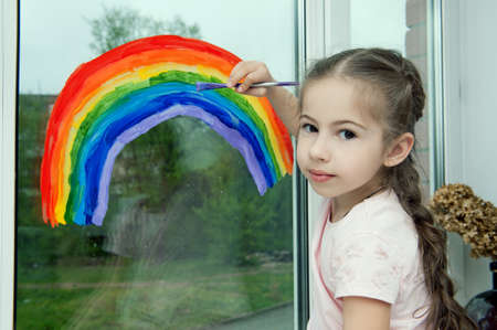 Little smiling girl sits by the window on the windowsill and draws a rainbow on the glass