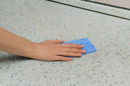 Kitchen cleaning: a female hand without a glove with a blue sponge wipes the countertop Stok Fotoğraf - 148948191