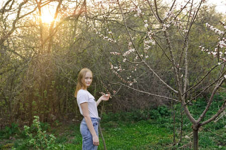 young girl, blonde in a blooming spring garden on a sunset background
