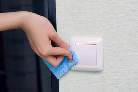 House cleaning: a female hand without a glove with a blue sponge wipes the dust on the switch Stok Fotoğraf - 149280714