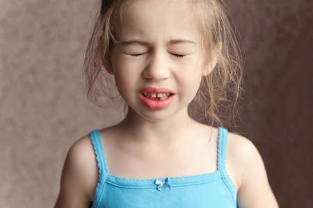 a child experiencing discomfort and pain from losing a baby tooth Stock Photo