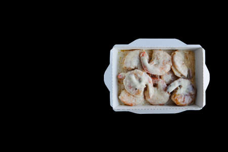 food with home delivery, shrimp in cream sauce in a disposable box on a black background, copyspace