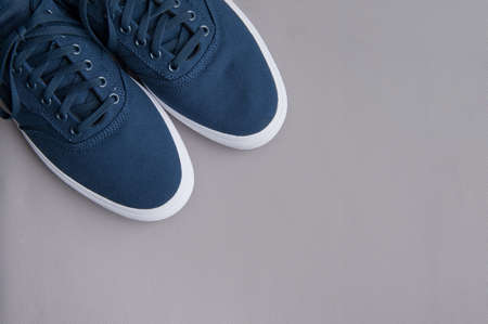 Blue textile sneakers with a white sole on a gray background. Flat lay Stok Fotoğraf - 151721953