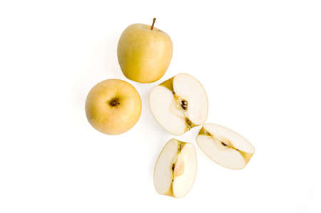 three yellow apples on a white background: two whole, one cut
