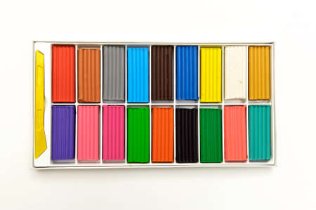 multi-colored plasticine in a box, 18 colors, on a white background, shot from above