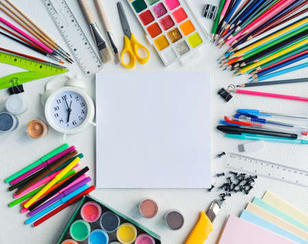 school supplies of different colors on a white background arranged in a circle, copy space