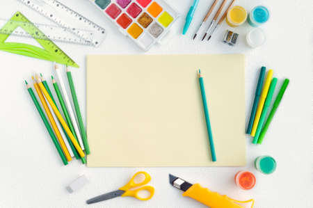 Blank yellow sheet of paper with colored school supplies Stok Fotoğraf - 152170940