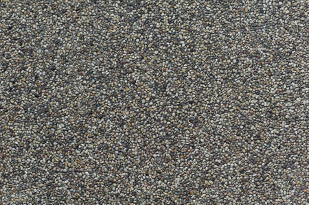 Closeup of exposed concrete made of small pebbles in different shades of brown and gray