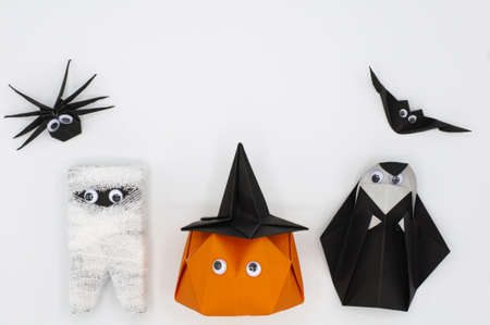 The Halloween origami (or Paper folding) of pumpkin head jack-o-lantern, mummy, nun, spider and bat isolated on white background with space for text. Stock Photo
