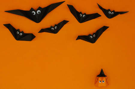 The origami Halloween background of pumpkin head jack-o-lantern looking up at the flying bats isolated on orange background with space for text.