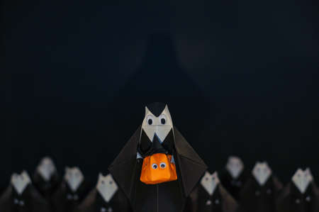 The Halloween origami (or Paper folding) Nun holding pumpkin head jack-o-lantern made from folded paper with many nuns at the back isolated on black background with space for text.