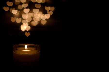 White aromatic glass candle with flame and heart shape bokeh on dark background for Christmas holiday.