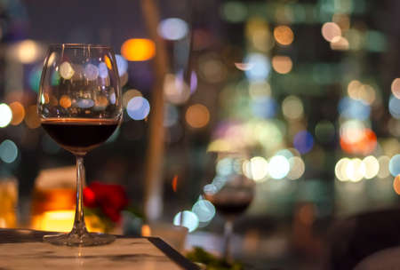 A glass of red wine on table of rooftop bar with colorful bokeh of city light and space for text.