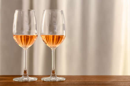 Two glasses of Rose wine on wooden table to celebrate for a couple with bright background of curtain in the house.