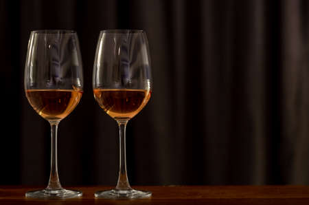 Two glasses of Rose wine on wooden table to celebrate for a couple with dark background of curtain in the house.