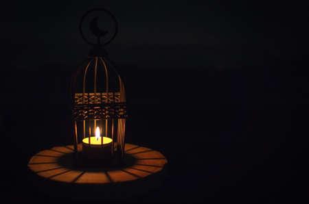 Belle lanterne qui a le symbole de la lune sur le dessus qui a la lumière de la bougie qui brille sur un plateau en bois avec un fond sombre pour la fête musulmane du mois sacré du Ramadan Kareem. Banque d'images
