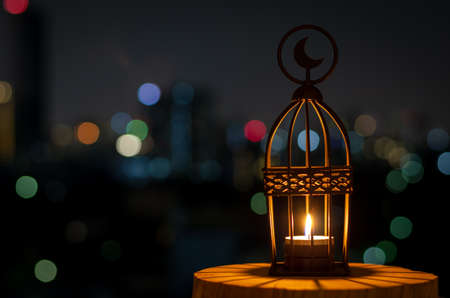 Beautiful Lantern that have moon symbol on top with city bokeh light on dark background for the Muslim feast of the holy month of Ramadan Kareem.