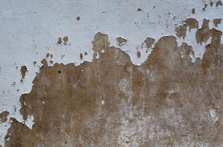Old and peeled of white painting cracked on the brown color cement wall surface for art background and textured photo.