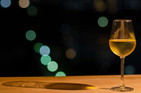 A glass of white wine and its shadow on wooden table of rooftop bar with colorful bokeh of city light and space for text. Standard-Bild