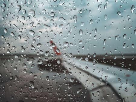 Rain drop at Airplane window before take off when monsoon season. Stock Photo - 128706278