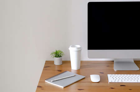 Modern personal computer screen on wooden table with a cup of coffee and Tillandsia air plant with space for text on white wall for working and office concept.