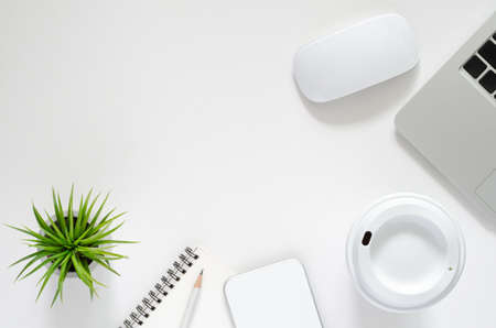 Modern workplace with laptop computer, wireless mouse, coffee cup, smartphone,  notebook, pencil and Tillandsia air plant on white background. Top view, flat lay concept.
