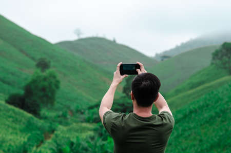 A male person using mobile phone taking a photo of greenery mountain with fog in the morning. 写真素材