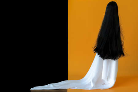 Long hair female ghost with white sheet costume with black and orange background. Minimal Halloween scary concept.