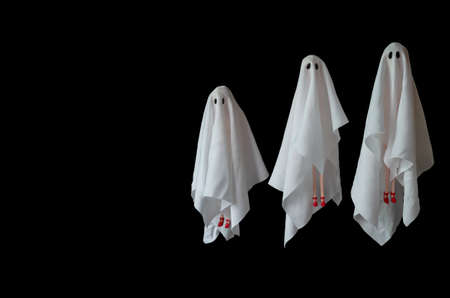 A group of female ghost white sheet costume flying in the air with black background. Minimal Halloween scary concept. Reklamní fotografie