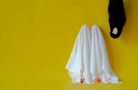 Two girl dolls cover with white sheet costume with female ghost head with long hair hanging from the top on yellow background. Minimal Halloween scary concept. Reklamní fotografie