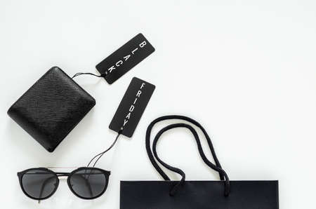Flat lay of men stuffs - black wallet, sunglasses, price tags and shopping bag on white background for Black Friday sale concept.