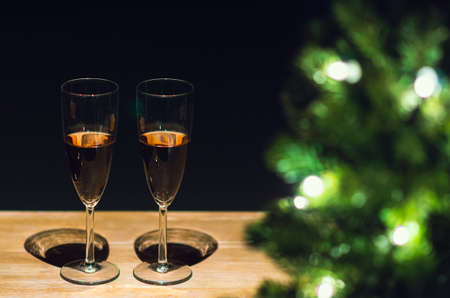 Two glasses of Rose wine on wooden table with Christmas tree and dark background. Stock Photo