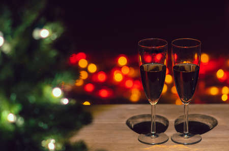 Two glasses of Rose wine on wooden table with Christmas tree and colorful bokeh light background. Stock Photo