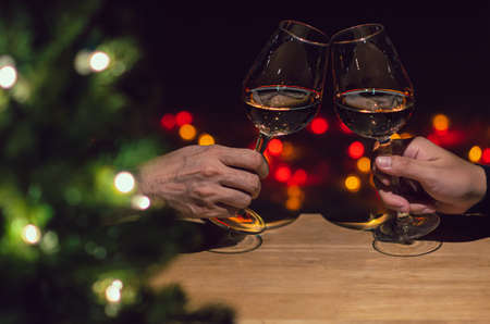 Two hands toasting glasses of Rose wine on wooden table with Christmas tree and colorful bokeh light background. Фото со стока
