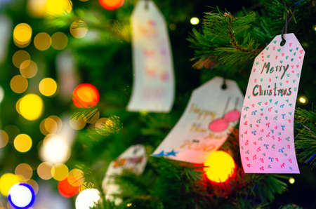 Paper hanging on Christmas tree for Holiday decoration with colorful lights on background.