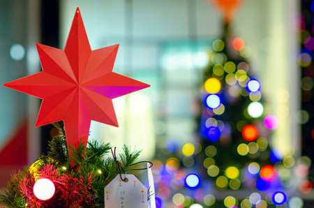 Star ornament puts on top of Christmas tree for Holiday decoration with colorful lights on background.