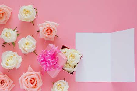 Roses roses et blanches sur fond rose avec boîte-cadeau rose et carte blanche vide pour la Saint-Valentin. Concept de fond plat. Banque d'images
