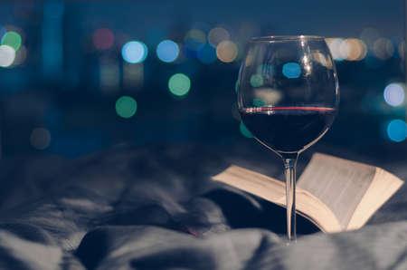 Ein Glas Rotwein mit Buch und buntem Bokeh aus dem Hintergrund der Stadtlichter aufs Bett gelegt.