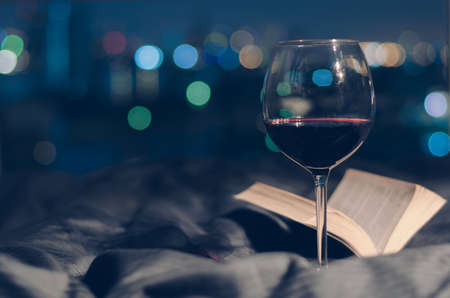 Un verre de vin rouge mis sur le lit avec un livre et un bokeh coloré sur fond de lumières de la ville.