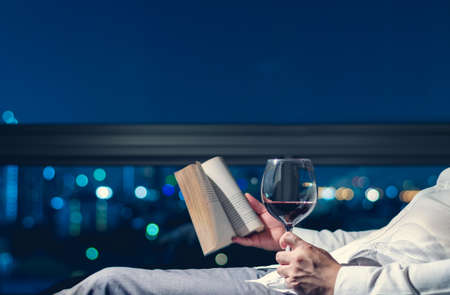 The man relaxing in the room reading book with a glass of red wine and background of city bokeh lights.