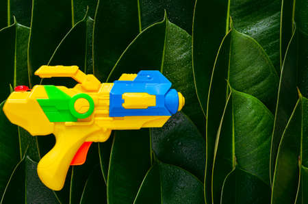 Yellow water gun put on green leaves background for Water or Songkran festival which celebrate in Thailand summer time on April.