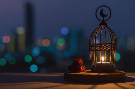 Lanterne qui a le symbole de la lune sur le dessus et les dates des fruits mis sur un plateau en bois avec des lumières colorées de bokeh de la ville pour la fête musulmane du mois sacré du Ramadan Kareem.