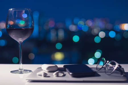 A glass of red wine put on table to enjoy the night after turning off laptop, smartphone and earphone for digital detox, social disconnect, gadget addiction concept.