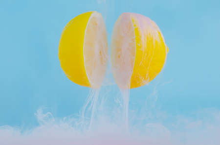 Blurred focus of dissolving pink poster color in water drop between two slice lemons on blue background for summer, abstract and background concept.
