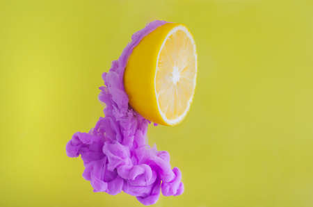 Slice lemon with partial focus of dissolving violet poster color in water on yellow background for summer, abstract and background concept.