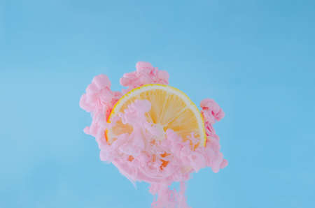 Slice lemon with partial focus of dissolving pink poster color in water on blue background for summer, abstract and background concept. 写真素材