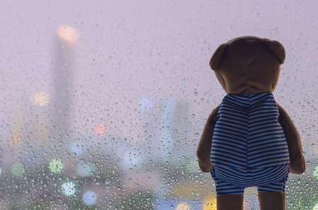 A lonely Teddy Bear looking out from glass window when raining at night with colorful city bokeh light background.