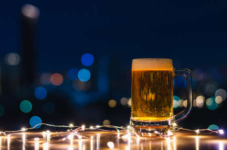 A glass of beer on wooden table with colorful city bokeh light background.