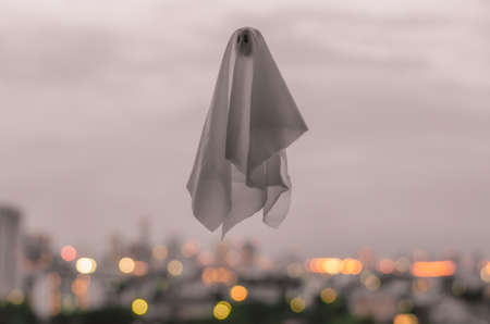White ghost sheet flying in dusk sky with city lights background. Halloween scary concept.