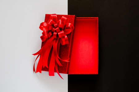 Red christmas box with red bow ribbon on black and white background. Black Friday concept.